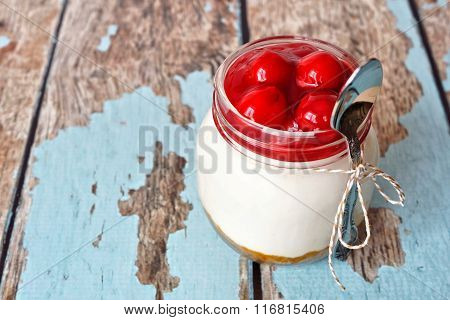 Cherry cheesecake in a mason jar with spoon