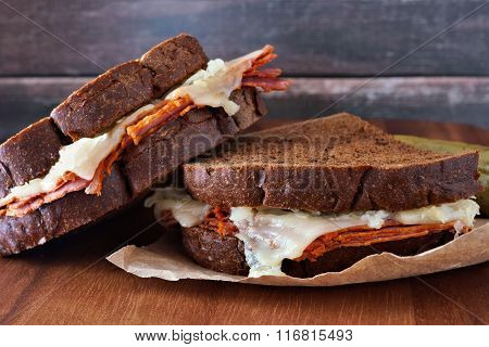 Reuben sandwiches stacked with rustic wood background