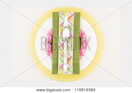 Top view of decorative spring place setting with green napkin, white plate and yellow charger with pink azaleas.