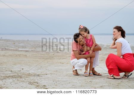 Happy Family Of Three Having Fun Sitting In The Sand On Beach