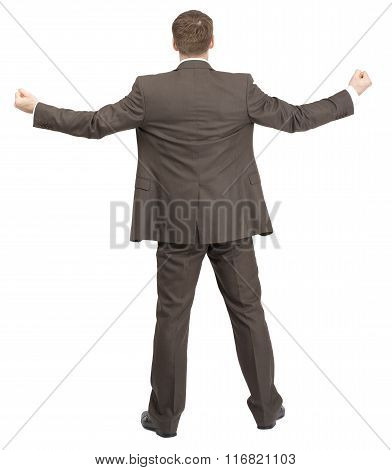 Businessman with spread arms and fists