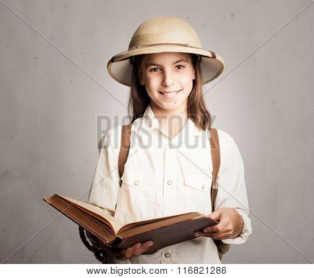 little explorer reading a book on a gray background
