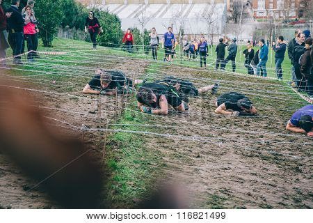 Runners crawling under barbed wire in a test of extreme obstacle race