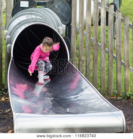 Young girl emerging from big slide