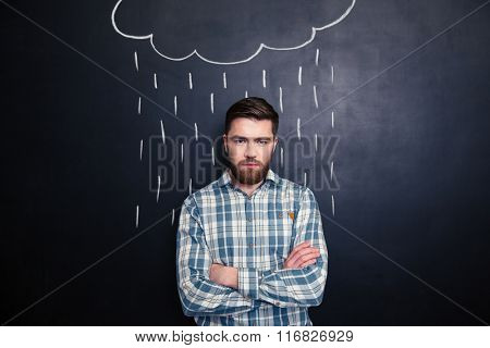 Serious handsome young man with beard standing with arms crossed under the drawn rain over background of chalkboard