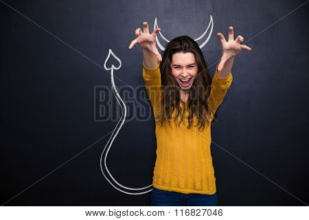 Shouting young woman with raised hands pretending devil standing over chalkboard background