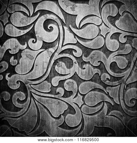 Black carved ornament on wooden texture