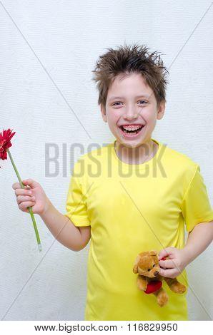Boy holding a flower and a teddy bear
