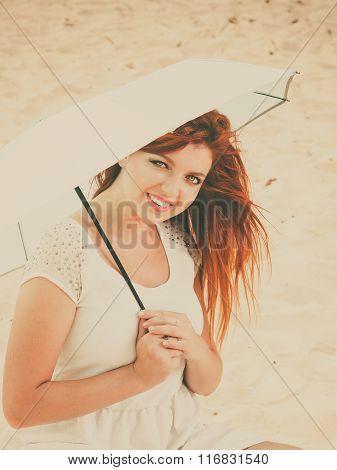 Redhaired Girl Sitting Under Umbrella On Beach.