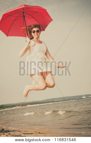 Girl Jumping With Red Umbrella On Beach.