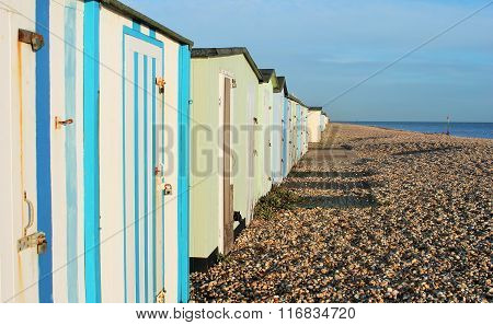 Traditional British beach huts at Uk seaside Brightly coloured beach huts