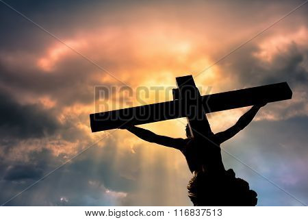 Christian Cross With Jesus Christ Statue Over Stormy Clouds