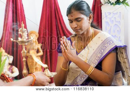Woman received prayers from priest. Traditional Indian Hindus ear piercing ceremony. India special rituals.