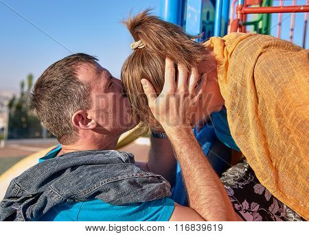 Young couple kisses outdoor in sunny day park