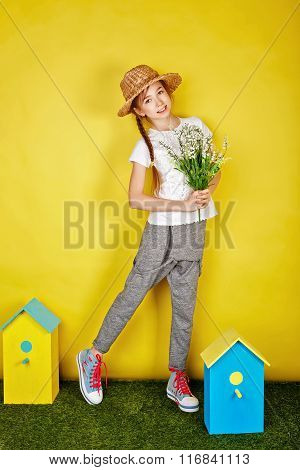 Teen Girl In Straw Hat Holding Spring Flowers.