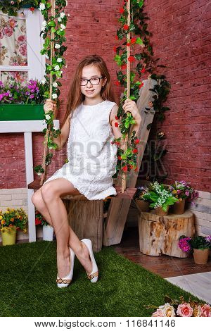 Teen Girl Sitting On A Swing.