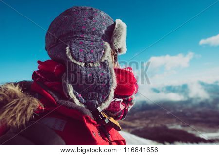 Young explorer looking away against blue sky, warm hat and scarf