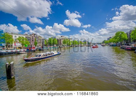 Amsterdam, Netherlands - July 10, 2015: Large water channel running through city with several boats
