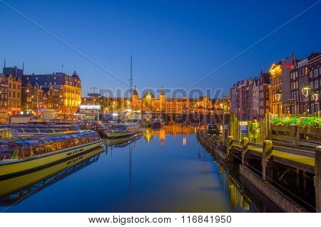 Amsterdam, Netherlands - July 10, 2015: Water channels by night, beautiful dark blue sky and city