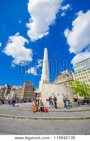 Amsterdam, Netherlands - July 10, 2015: Dam Square on a beautiful sunny day, tall monument and histo