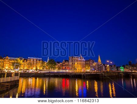 Amsterdam, Netherlands - July 10, 2015: Water channels by night, beautiful dark blue sky and city li