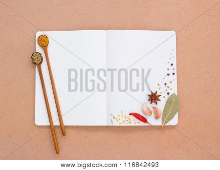 Note Book That The Device Is Equipped With Cooking Consists Of Aromatic Herbs On Brown Wood..