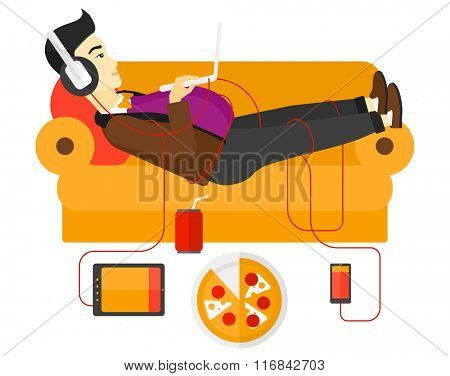 Man with gadgets lying on sofa.