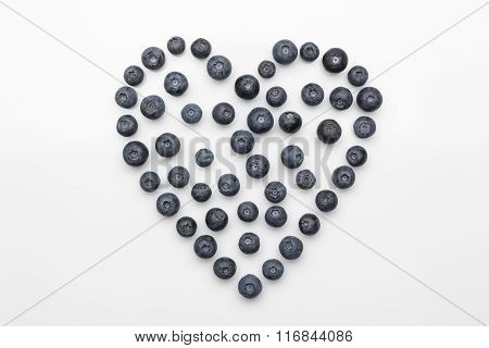 Blueberries heart from above on white