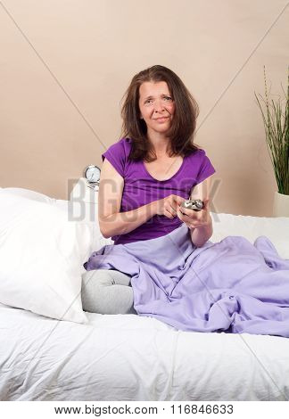 woman with alarmclock on the bed at the morning
