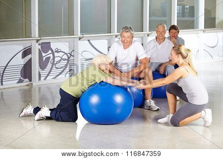 Fitness instructor helping senior woman with gym ball in rehab center