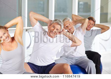 Happy senior group doing back training on gym balls in fitness center