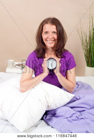 Smiling woman holding an alarm clock