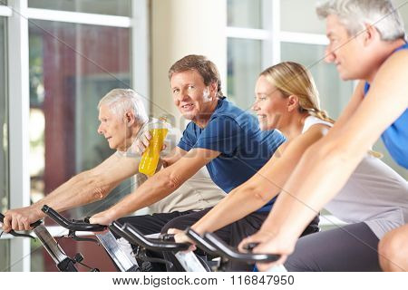 Thirsty man drinking soda on spinning bike in a gym