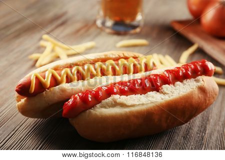 Hot dogs with fried potatoes and onions on wooden background