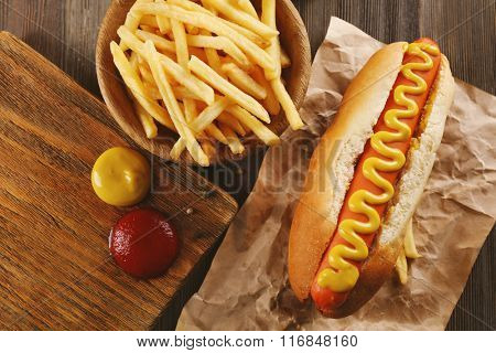 Hot dog with fried potatoes on craft paper closeup