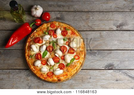 Delicious pizza and fresh vegetables on wooden background, close up