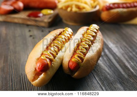 Hot dogs with fried potatoes and fresh sausages on wooden background