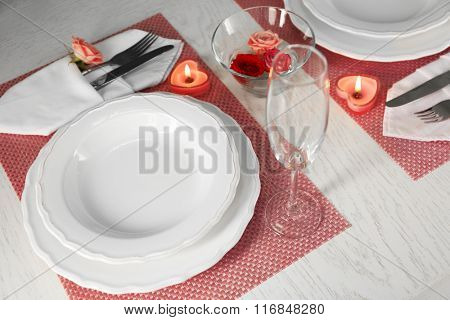 Table setting for two person with dishes and cutlery on pink napkin