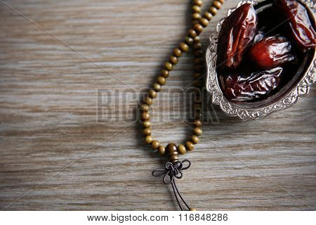 Dry dates and rosary on a wooden table