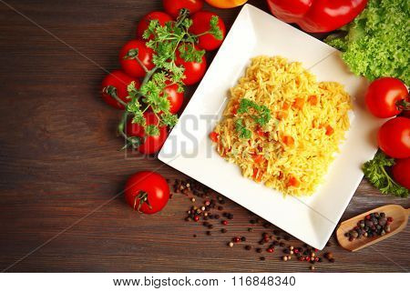 Dish of vegetarian rice on wooden table, top view