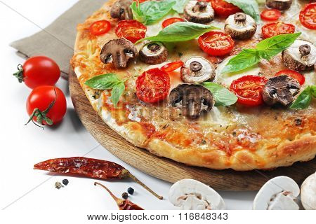 Tasty pizza and fresh vegetables on round wooden board, close up