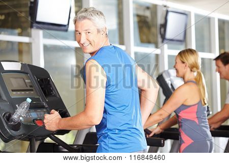 Happy senior man training in a fitness center on the treadmill
