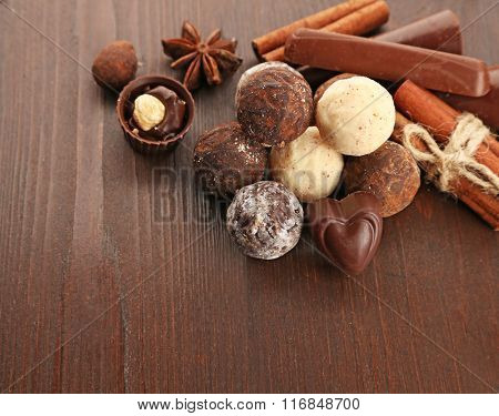 Assorted chocolate candies on a wooden background, close up