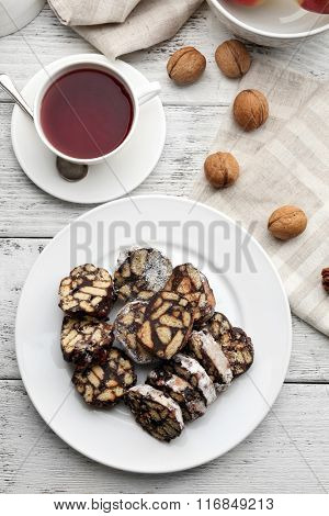 Chocolate salami in a plate over wooden background, close up