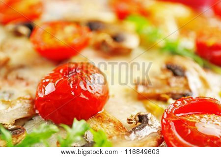 Macro view of freshly homemade pizza with cherry tomatoes and mushrooms