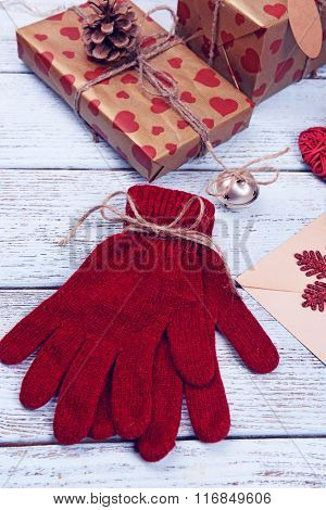 Composition of Christmas gifts, warm gloves and pile of envelops on white wooden background