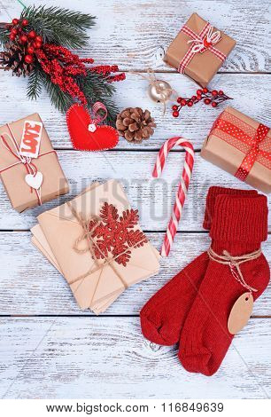 Warm woolen socks with Christmas gifts and decorations on white  wooden background, close up