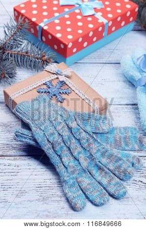 Composition of warm socks and gloves with Christmas gifts on white wooden background, close up
