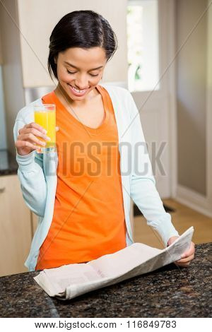 Smiling brunette reading newspaper and holding glass with orange juice in the kitchen