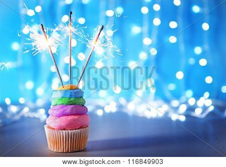 Cupcake with varicolored cream icing and sparklers on a glitter background